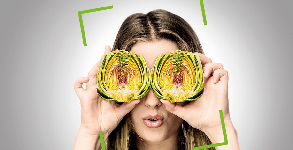 Frau hält sich zwei Salathälften vor die Augen.