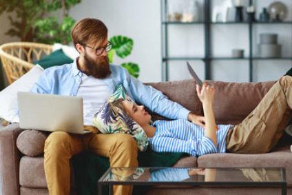 Pärchen mit Tablet und Computer auf dem Sofa.