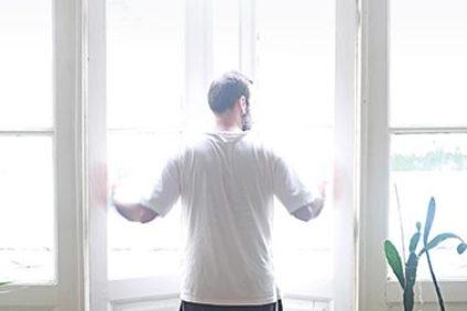 Ein Mann öffnet ein Fenster.