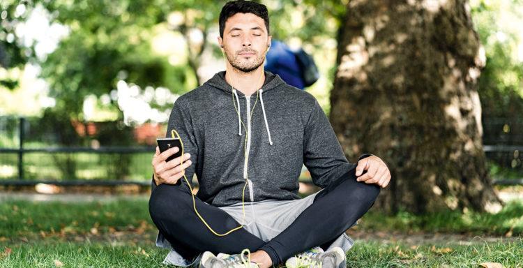 Junger Mann in Sportkleidung entspannt mit einer Meditationsapp im Park.