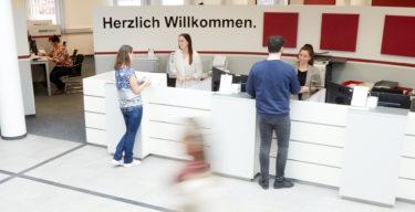 Mitarbeiter der BMW BKK bedienen am Empfangstresen Kunden.