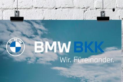 Eine Postkarte, bedruckt mit Himmel, Wolken, dem BMW- und dem BMW BKK-Logo, hängt an der Wand.