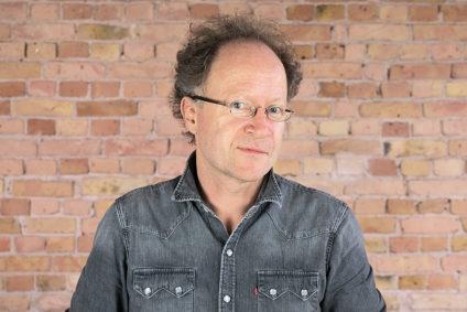 Dr. Martin Hirsch vor einer Ziegelwand.