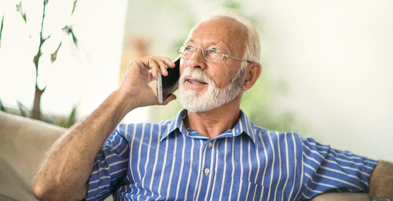 Ein älterer Mann telefoniert zuhause mit seinem Handy.