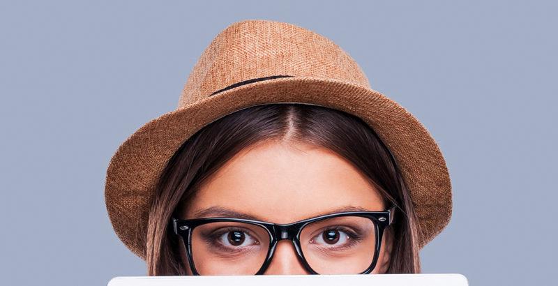 Junge Frau mit Brille und Strohhut blickt über den Rand ihres Tablets.