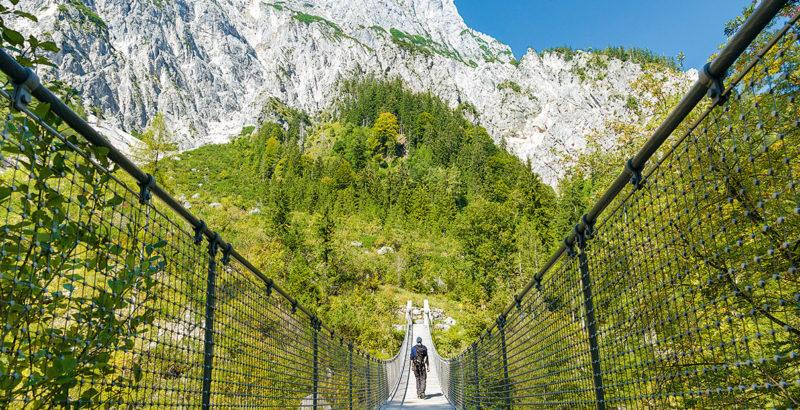 Ein Wanderer begeht eine lange Hängebrücke vor einem Gipfelmassiv.