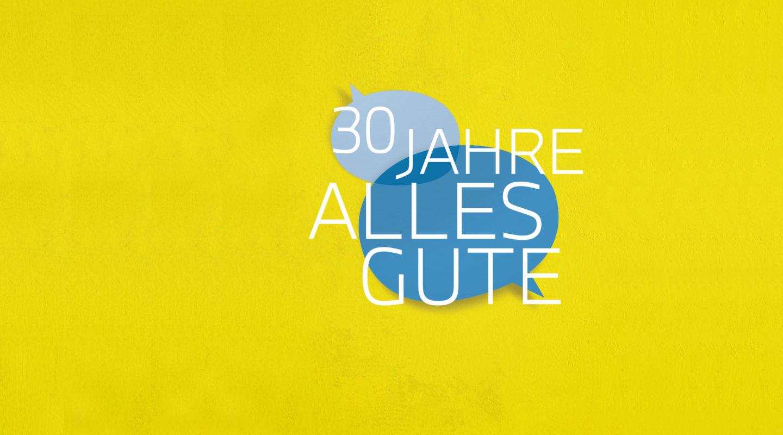 """Schriftzug """"30 Jahre Alles Gute"""" über zwei blauen Sprechblasen auf gelbem Hintergrund."""