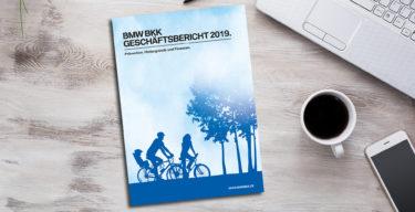 Der BMW BKK Geschäftsbericht 2019 liegt neben einer Tasse Kaffee, Handy und PC auf einem Tisch.