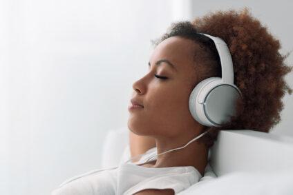 Eine Frau liegt mit Kopfhörern entspannt auf der Couch.
