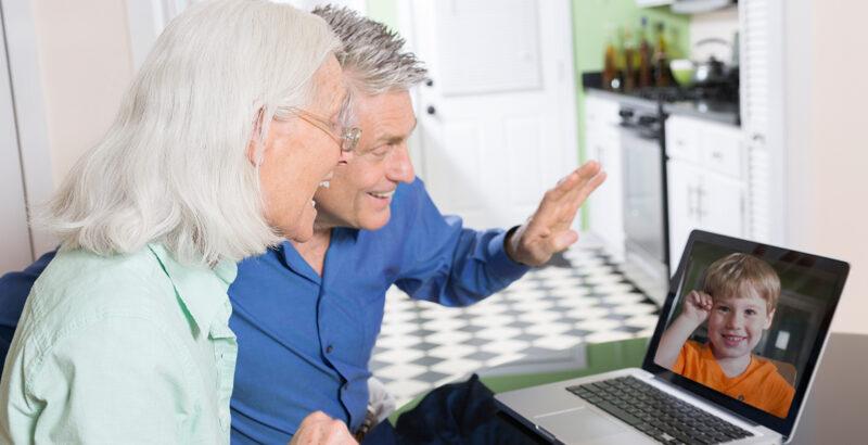 Ein älteres Paar spricht per Videochat mit ihrem Enkelsohn.