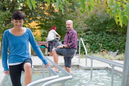 Ein Mann und eine Frau laufen durch ein Kneipp-Bad.
