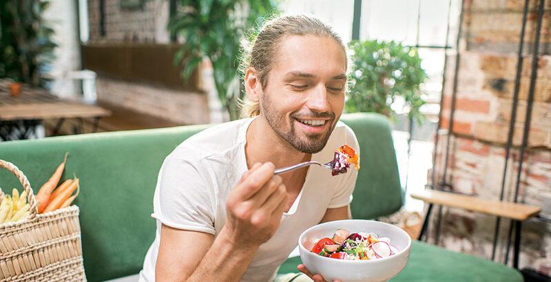 Junger Mann auf der Couch isst einen Salat.