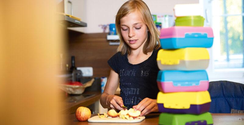 Mädchen schneidet einen Apfel, neben ihr hoher Stapel an Brotboxen.